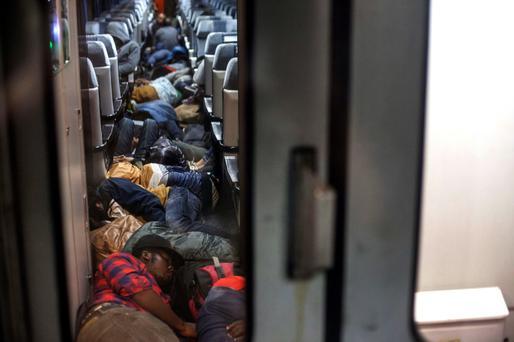 Migrants sleep on a train bound for the northern Serbian city of Subotica, near the border with Hungary; this year, more than 50,000 migrants tried to cross into Hungary via Serbia. Photo: AFP / Igor Pavicevic