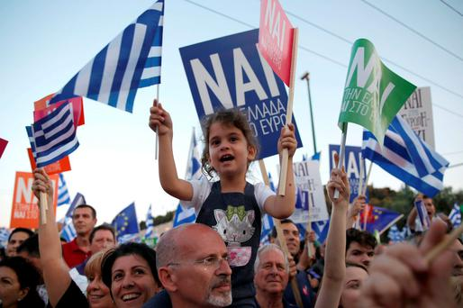 'Yes' supporter wave Greek flags at a rally in Athens
