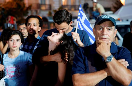 No voters kiss as they celebrate the results of the first exit polls in front of the Greek parliament in Syntagma Square in Athens last night