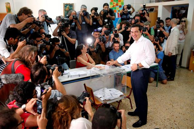 Greek Prime Minister Alexis Tsipras casts his ballot at a polling station in Athens yesterday