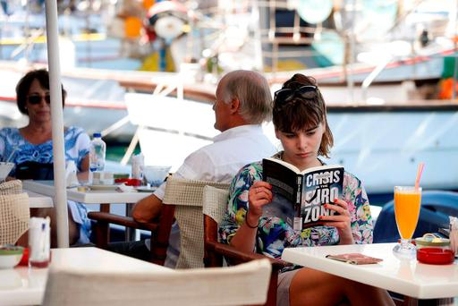 A woman reads a book in the village of Meyisti, on the Island of Kastellorizo, which is the most easterly of the islands in Greece