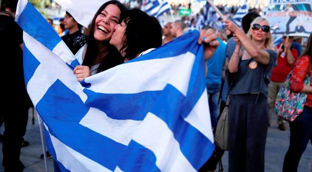 Anti-austerity 'No' voters celebrate the results of the first exit polls in front of the Greek parliament in Syntagma Square in Athens last night