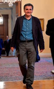 Finance Minister Euclid Tsakalotos arrives at the presidential palace in Athens yesterday