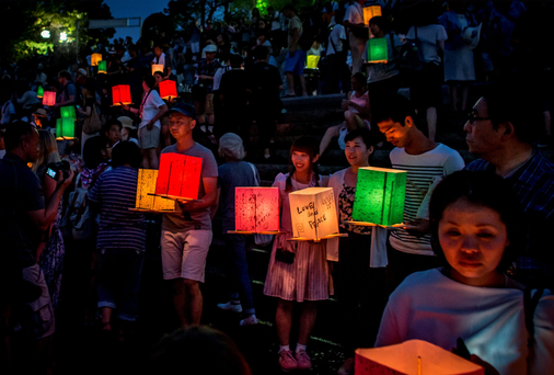 People wait to float candle lit lanterns to commemorate the 70th anniversary of the atomic bombing of Hiroshima at the Hiroshima Peace Memorial Park.