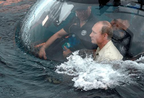 President Vladimir Putin, right, sits on board a submarine as it plunges into the Black Sea yesterday