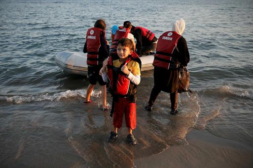 A migrant boy removes his lifejacket, moments after arriving on a dinghy with his family on the Greek island of Kos