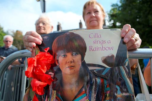 A fan holds the cover of an old Cilla Black LP outside St Mary's Catholic Church