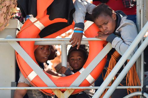 Migrants wait to disembark from the LE Niamh at the Messina harbour in Sicily, Italy