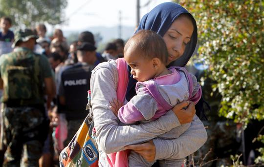 A woman with a baby enters Macedonia from Greece on the border line between the two countries, near southern Macedonia's town of Gevgelija