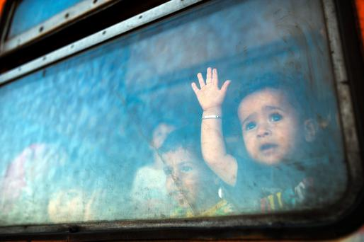 A migrant boy looks through a window on board a train bound for Serbia at the new transit centre for migrants at the border between Greece and Macedonia, near the town of Gevgelija