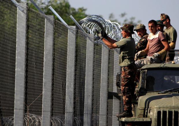 Hungarian soldiers adjust the razor wire on a fence near the town of Asotthalom, Hungary.