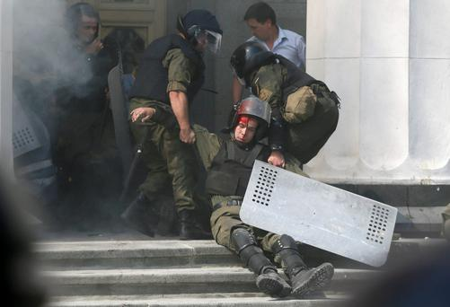 An injured national guard officer is carried away by comrades outside the parliament building in Kiev, Ukraine, August 31, 2015. Nearly 90 people were wounded and several of them were in a serious condition yesterday.