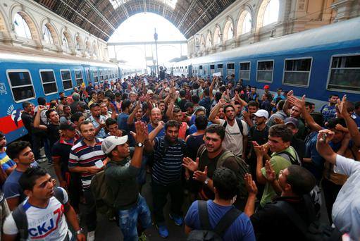 Migrants gesture as they stand in the main Eastern Railway station in Budapest, Hungary, yesterday. Hungary closed Budapest's main Eastern Railway station with no trains departing or arriving until further notice.