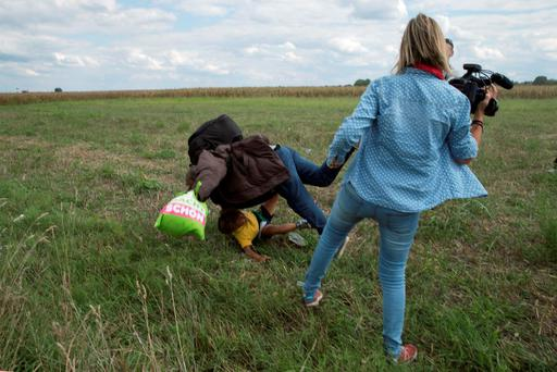 A migrant carrying a child falls after tripping on TV camerawoman (R) Petra Laszlo while trying to escape from a collection point in Roszke village, Hungary