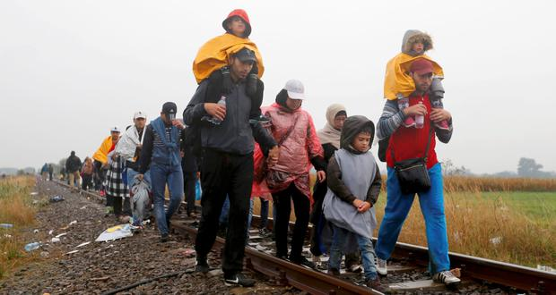 Migrants walk along a rail track in the rain from Roszke to Szeged in Hungary.