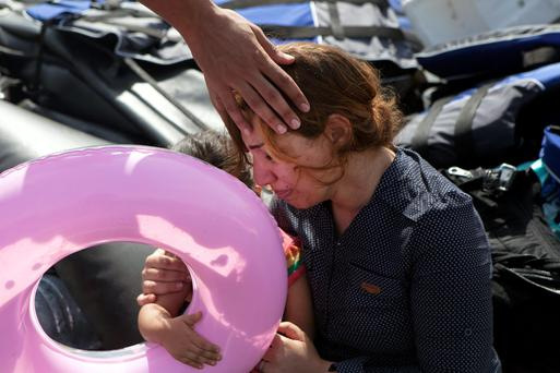 A Syrian refugee holding her child is comforted moments after arriving on a dinghy on the Greek island of Lesbos. Photo: Dimitris Michalakis