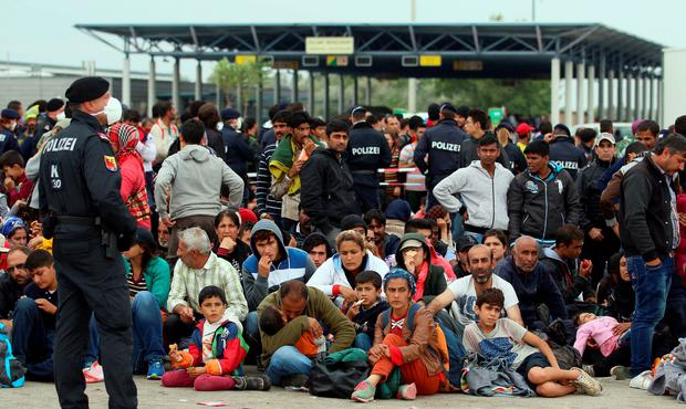Refugees rest after crossing the border between Hungary and Austria in Nickelsdorf yesterday.