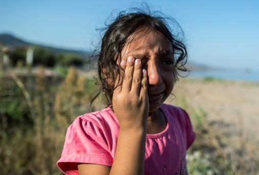 A Syrian refugee cries after arriving on the Greek island of Kos