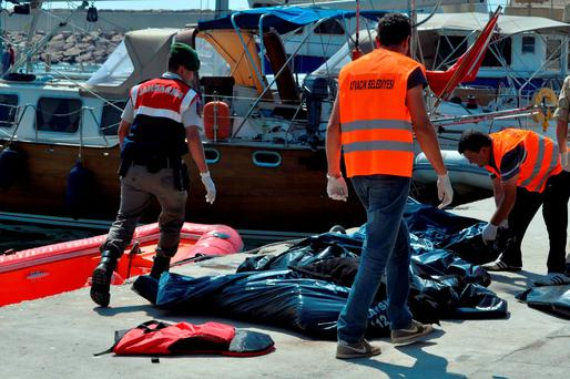 Local workers collect the bodies of migrants on the shore after 13 died in a collision between a boat carrying refugees and a ferry off the Turkish coast near Ayvacik, Canakkale