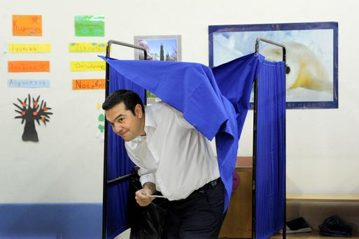 Former Greek prime minister Alexis Tsipras holds his ballot as he exits a voting booth in Athens