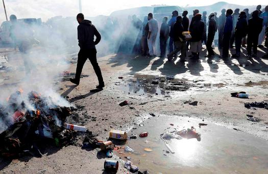 Smoke rises from burning rubbish as migrants queue for food at the makeshift camp called 'The New Jungle' in Calais, France
