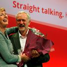 Britain's Labour Party leader Jeremy Corbyn presents former acting leader Harriet Harman with flowers, as she leaves the stage at the party's annual conference in Brighton