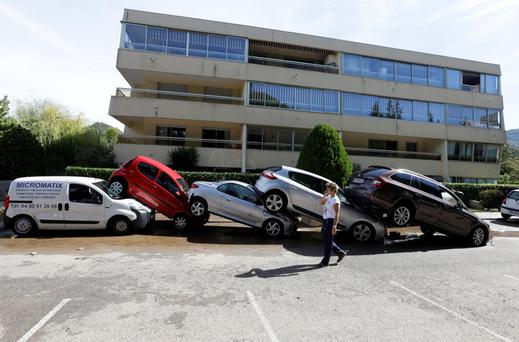 A man walks by cars pile up after floods in Mandelieu la Napoule, near Cannes, in southern France