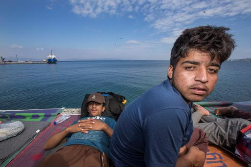 Tired migrants rest after arriving in Kos