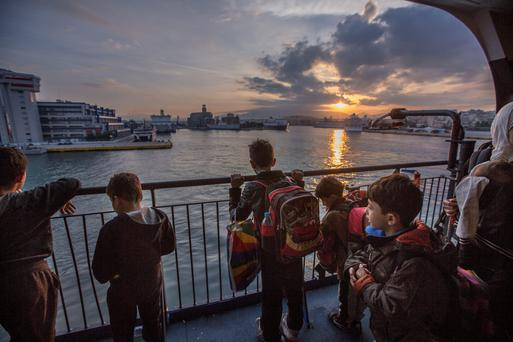 Syrian migrant children arrive to a new dawn as their ferry docks in Athens from Kos. Picture: Mark Condren