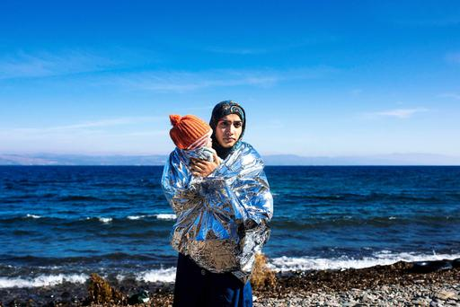 A woman holds her child wrapped in an emergency blanket shortly after arriving with other refugees on the Greek island of Lesbos after crossing the Aegean Sea from Turkey yesterday. Four migrants, including children, died yesterday near Lesbos after their boat collided with a Greek rescue vessel, the coastguard said