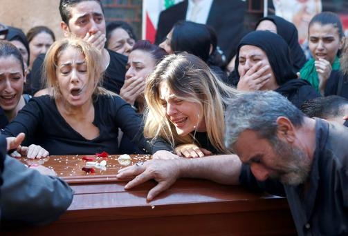 Relatives of the Safwan family, that drowned on a boat carrying them from Turkey to Greece, mourn on their coffins during their funeral in Beirut's southern suburb of Ouzai, Lebanon yesterday.