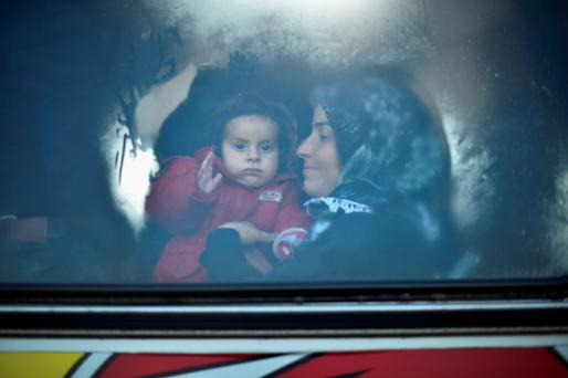 Migrants sit inside buses, as they are transported to Brezice refugee camp in Rigonce, Slovenia.