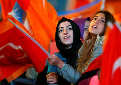 Women wave flags outside the AK Party headquarters in Ankara, Turkey November 2, 2015. Turkish Prime Minister Ahmet Davutoglu described the outcome of a general election which swept his AK Party back to a parliamentary majority on Sunday as a victory for d