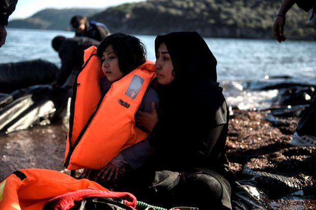 A refugee mother and her child on the shore on the Greek island of Lesbos after crossing the Aegean Sea from Turkey yesterday