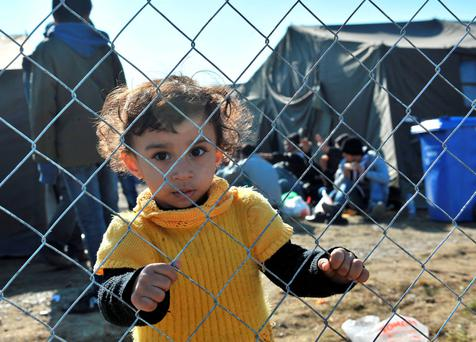A girl holds on to a fence at a transit camp housing migrants and refugees in Slavonski Brod. Photo: AFP/Getty Images