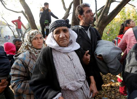 A woman from Kobani in Syria, 87, looks on as migrants queue to cross the border into Spielfeld in Austria from the village of Sentilj, Slovenia.