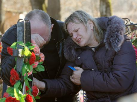 Nina Lushchenko's nephew Pavel and daughter Veronika react at her grave, after her funeral at a cemetery in the village of Sitnya, 80 km (about 50 miles) of Veliky Novgorod, Russia.