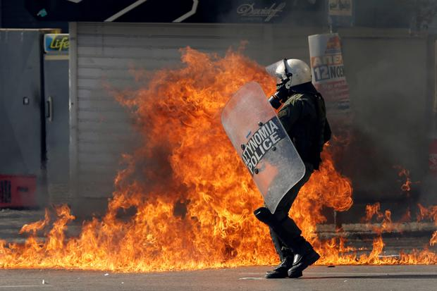 A riot policeman tries to avoid a petrol bomb thrown by protesters during a rally in Athens