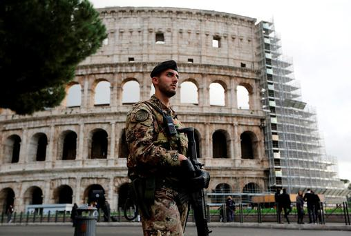 An Italian army soldier patrols in front of Rome's Colosseum. Authorities in charge of Rome's Colosseum will install metal detectors at the entrance to the almost 2,000 year-old amphitheatre as cities across Europe tighten security in the wake of last week's deadly attacks in Paris