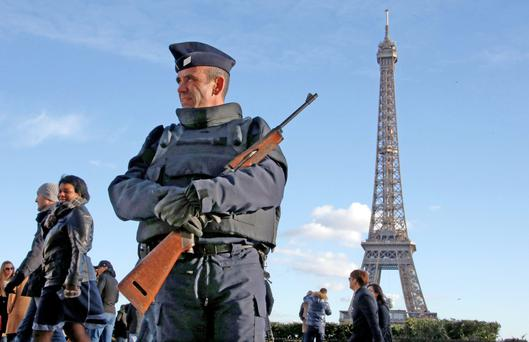 A French police officer stands guard by the Eiffel tower