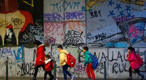 Children walk past graffiti on their way to school, in central Brussels. Photo: Reuters