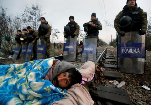 Stranded Iranian migrant on hunger strike looks on after waking-up in front of Macedonian riot police at the border between Greece and Macedonia near the Greek village of Idomeni yesterday.