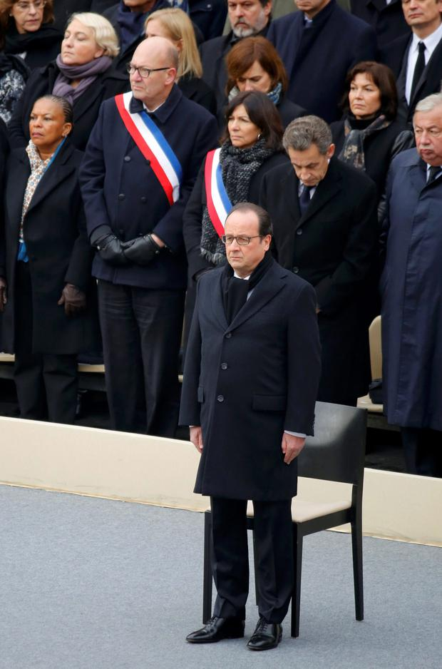 French President Francois Hollande stands in front of members of the French government, officials and guests during a ceremony to pay a national homage to the victims of the Paris attacks at Les Invalides monument in Paris,.
