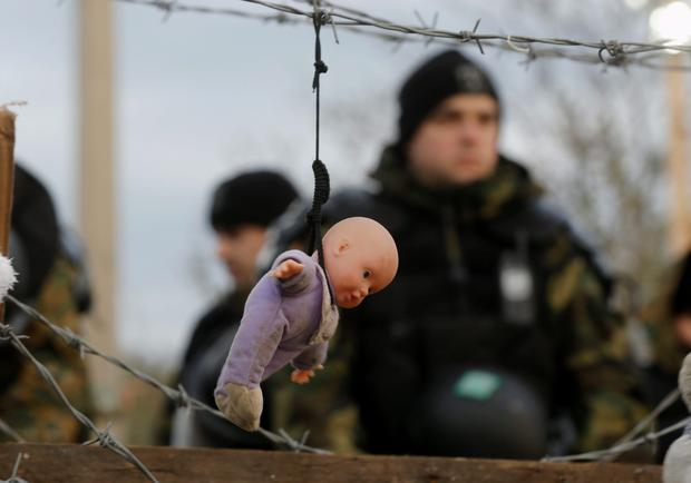 A doll, placed by stranded Iranian migrant protesters, hangs from barbed wire in front of Macedonian police at the Greek-Macedonian border near to the Greek village of Idomen. The migrants have been denied entry into Macedonia.