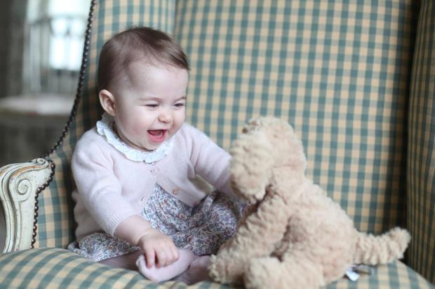 Princess Charlotte laughs with her teddy in this photograph taken by her mother Kate, Duchess of Cambridge