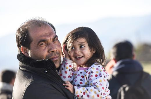 A migrant holds his daughter as they wait to enter the camp after crossing the Greek-Macedonian border, near Gevgelija, on November 30, 2015