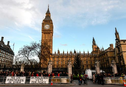 Protesters put up anti-war banners next to the Houses of Parliament as a debate is held over airstrikes in Syria on December 2, 2015 in London, England. The debate is expected to last all day with a vote on possible British airstrikes on Islamic State targets in Syria taking place.