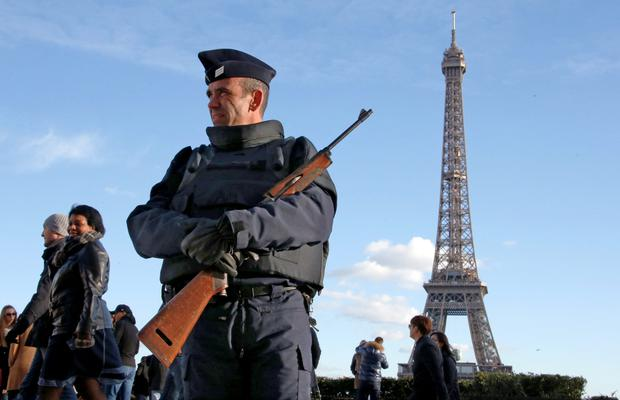 A French police officer stood guard by the Eiffel Tower as Paris remained on high alert after the November 13 attacks.