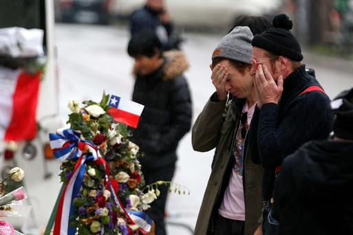 Jesse Hughes (R) and Julian Dorio, members of Eagles of Death Metal band, mourn in front of the Bataclan this week.