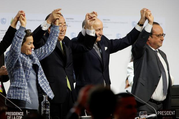 President of COP21 Laurent Fabius (centre) raises hands with UN secretary general Ban Ki Moon (second left) and French President François Hollande (right) after adoption of a historic global warming pact at the COP21 Climate Conference in Paris